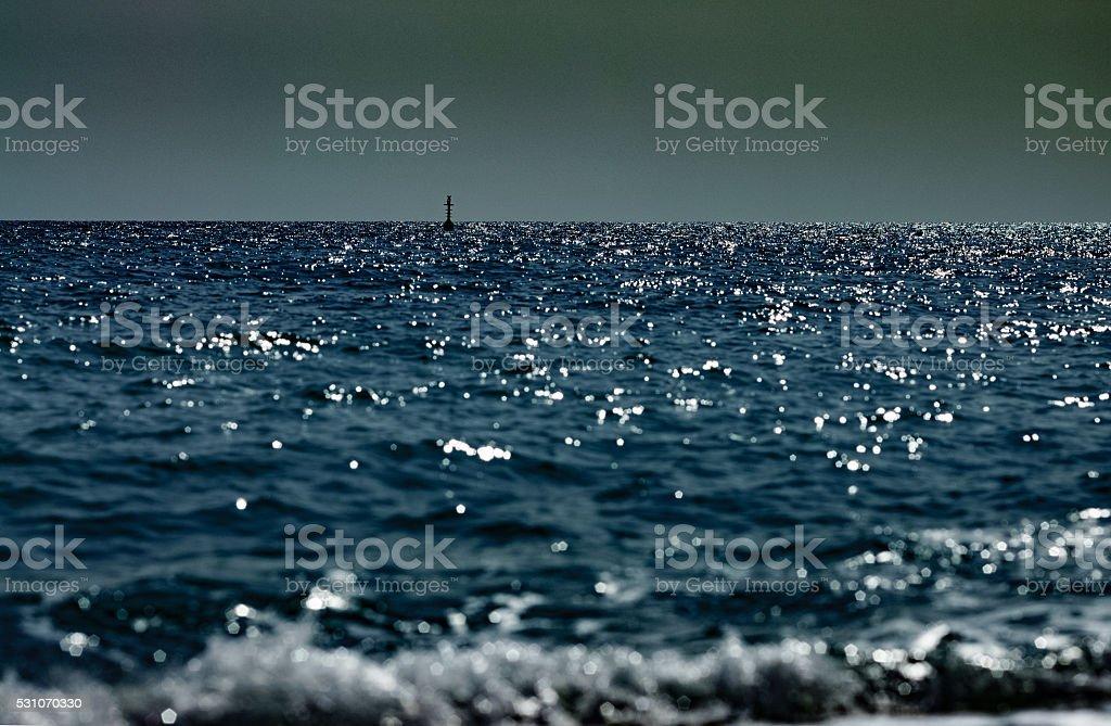 Deep dark seascape with one buoy on the horizon stock photo