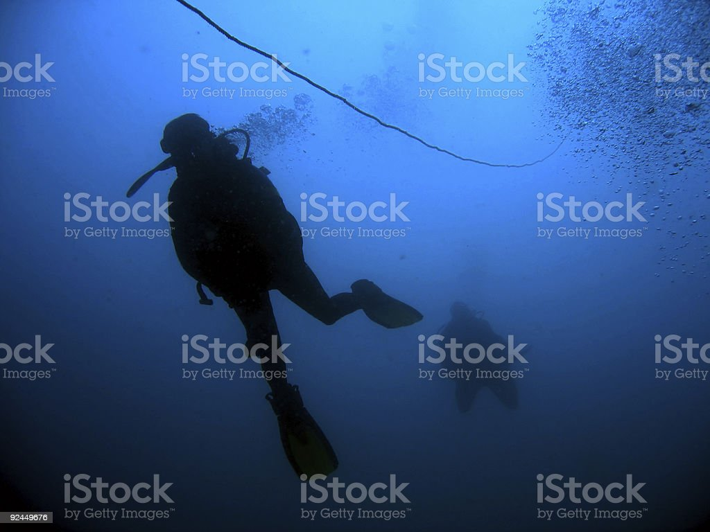 deep dark water scuba divers descent royalty-free stock photo