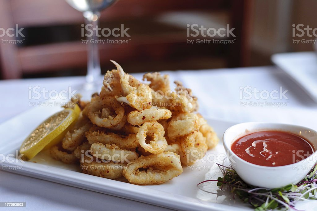 Deep fried calamari with lemon slices and red dipping sauce royalty-free stock photo