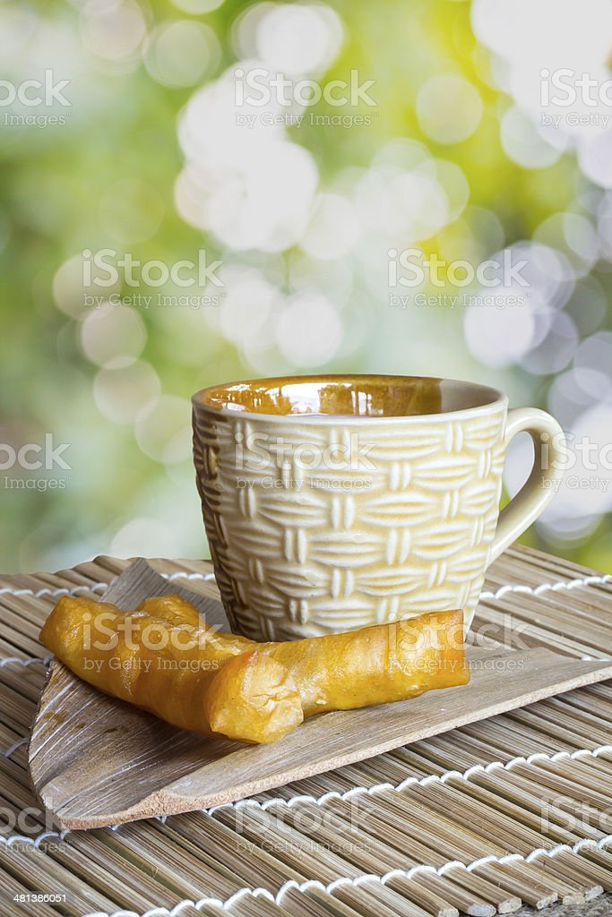Deep fried dough sticks and a cup royalty-free stock photo