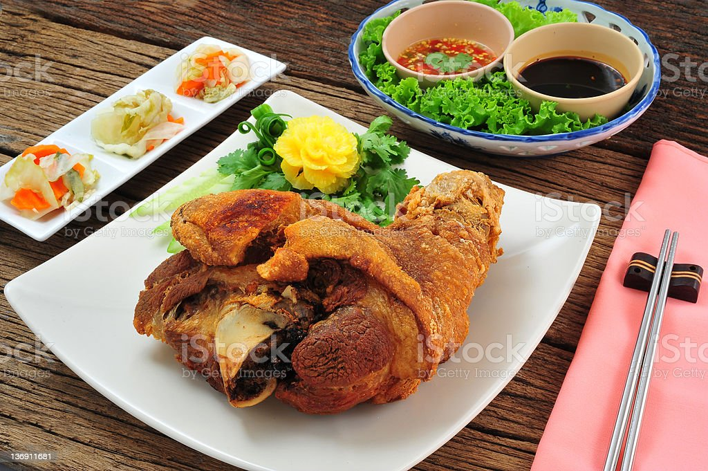 Deep fried pig thigh on square plate and wooden table royalty-free stock photo