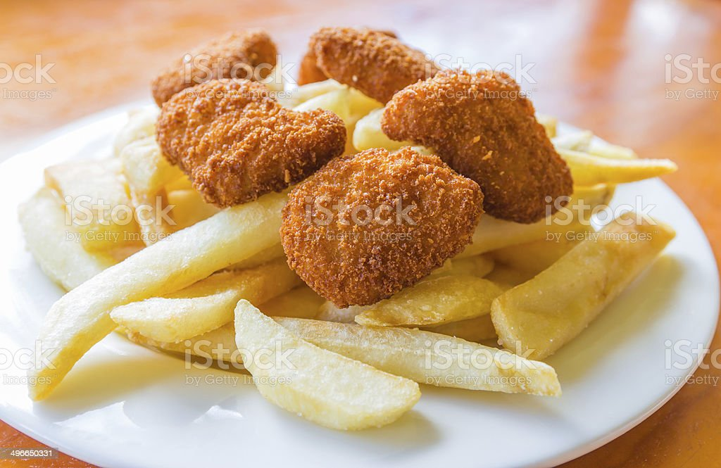 Deep fried potato chips and chicken nuggets stock photo