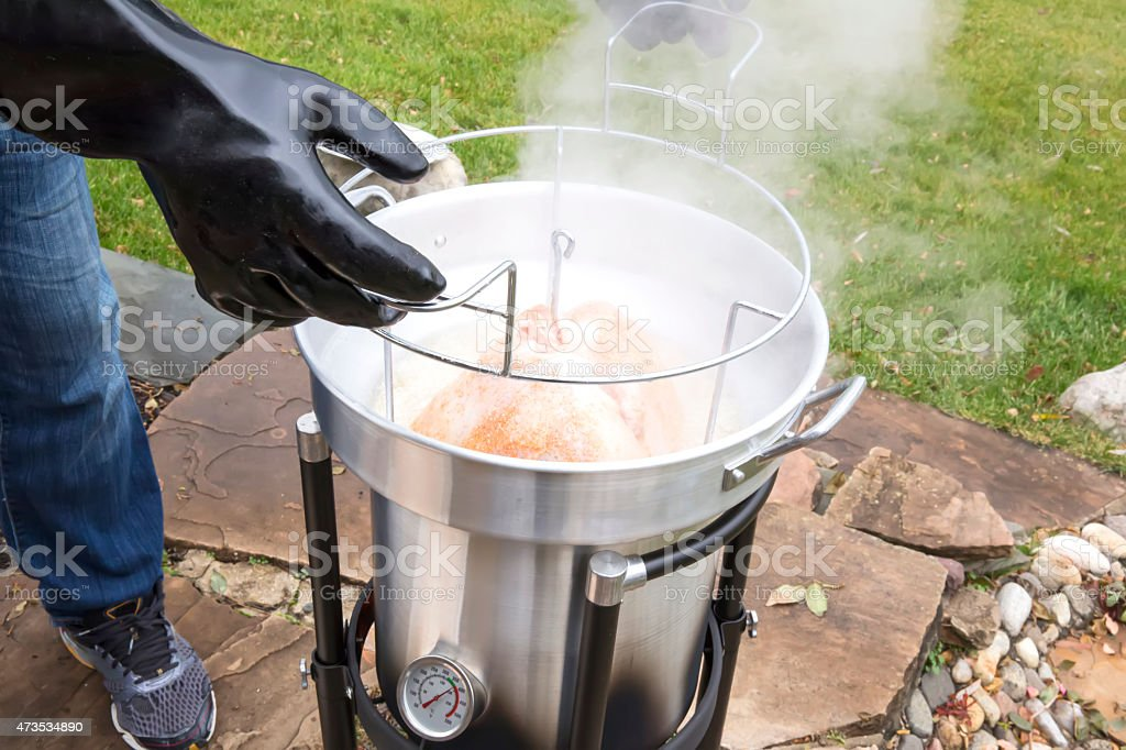 Deep fried Thanksgiving turkey being taken out of fryer stock photo