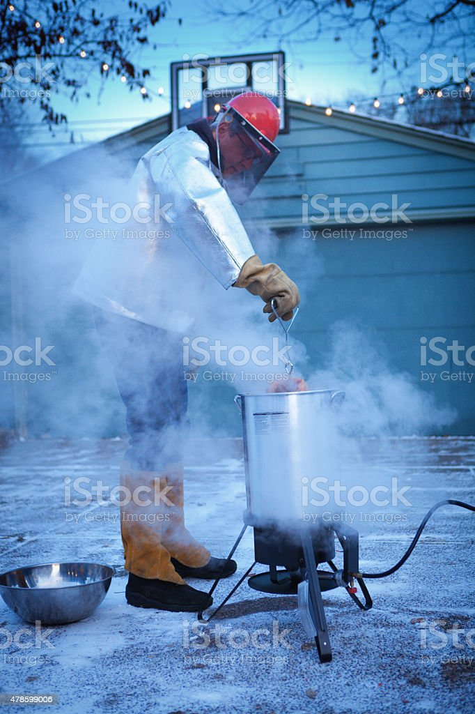 Deep Frying Turkey in Hot Oil for Christmas and Thanksgiving stock photo