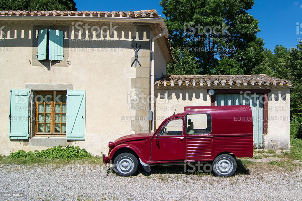 Deep red 2CV van standing in front of a house stock photo