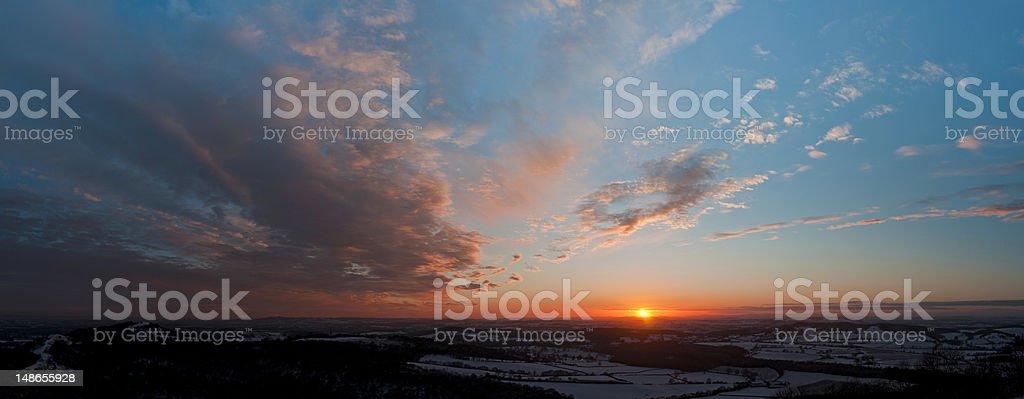 Deep red sunset panorama dramatic vibrant cloudscape idyllic patchwork landscape stock photo