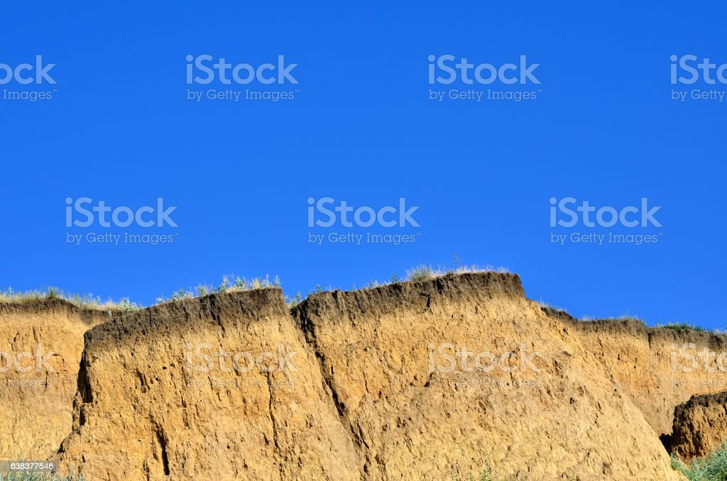 Deep sandy cliff on the background of blue sky. stock photo
