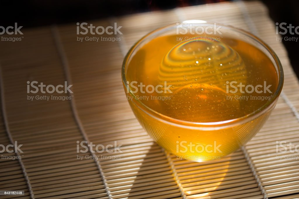 deep saucer of honey on the table, illuminated by the sun stock photo