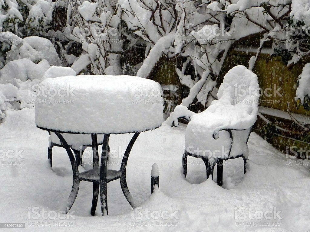 Deep snow covers garden table, chairs and plants stock photo