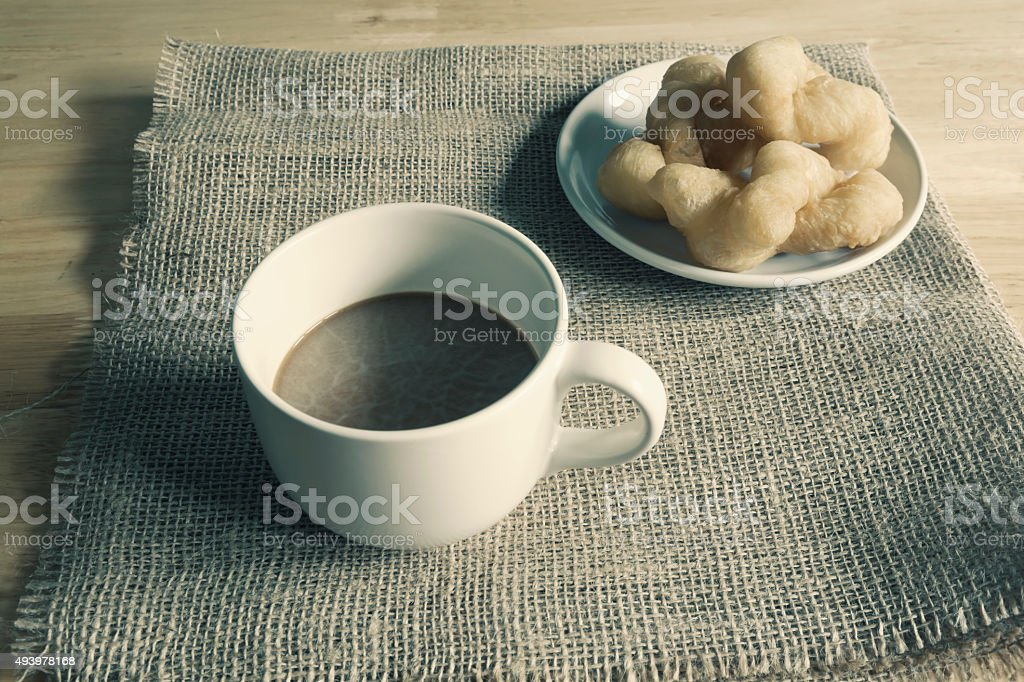 Deep-fried dough stick and cup of coffee royalty-free stock photo