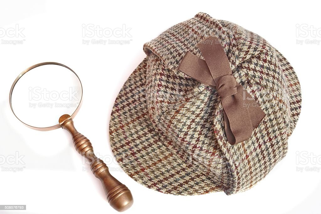 Deerstalker Hat And Magnifying Glass On Wooden Table stock photo