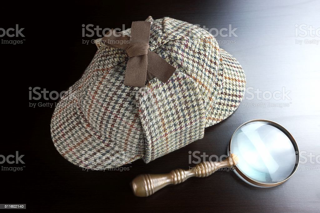 Sherlock Deerstalker Hat,   And Vintage  Magnifying Glass On Bla stock photo