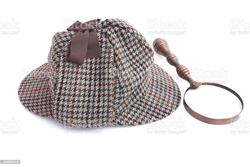 Deerstalker or Cap or Hat and vintage magnifying glass stock photo
