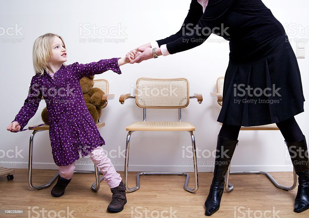 Defiant Little Girl Resisting Mother in Waiting Room stock photo