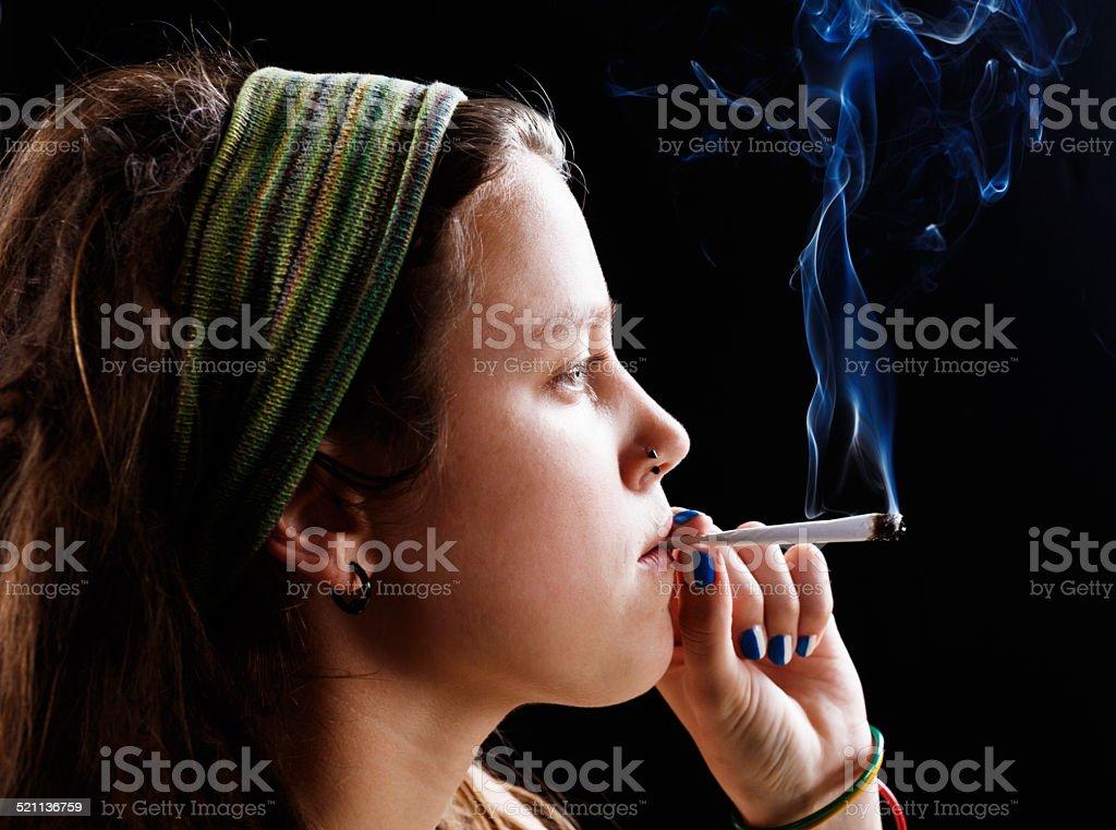 Defiant young hippie smokes her marijuana stock photo