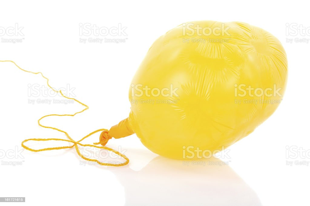 Deflated yellow balloon at a rope; isolated over white stock photo