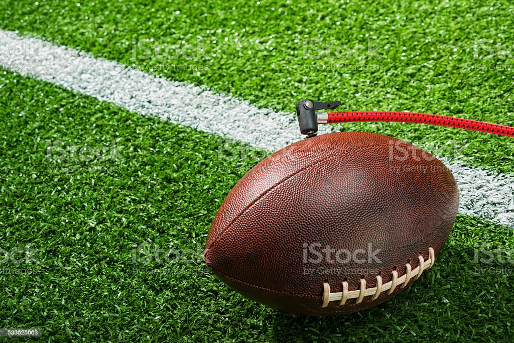 Deflate-Gate. Football deflated on the field stock photo