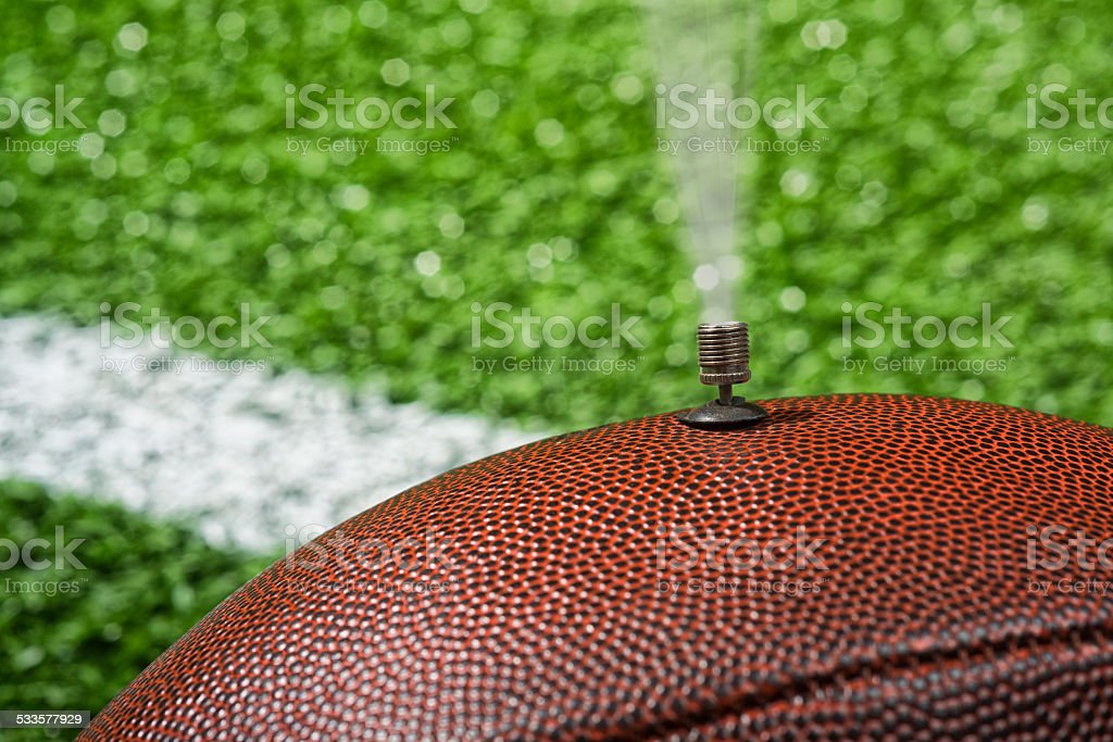 Deflate-Gate. NFL football deflated on the field stock photo