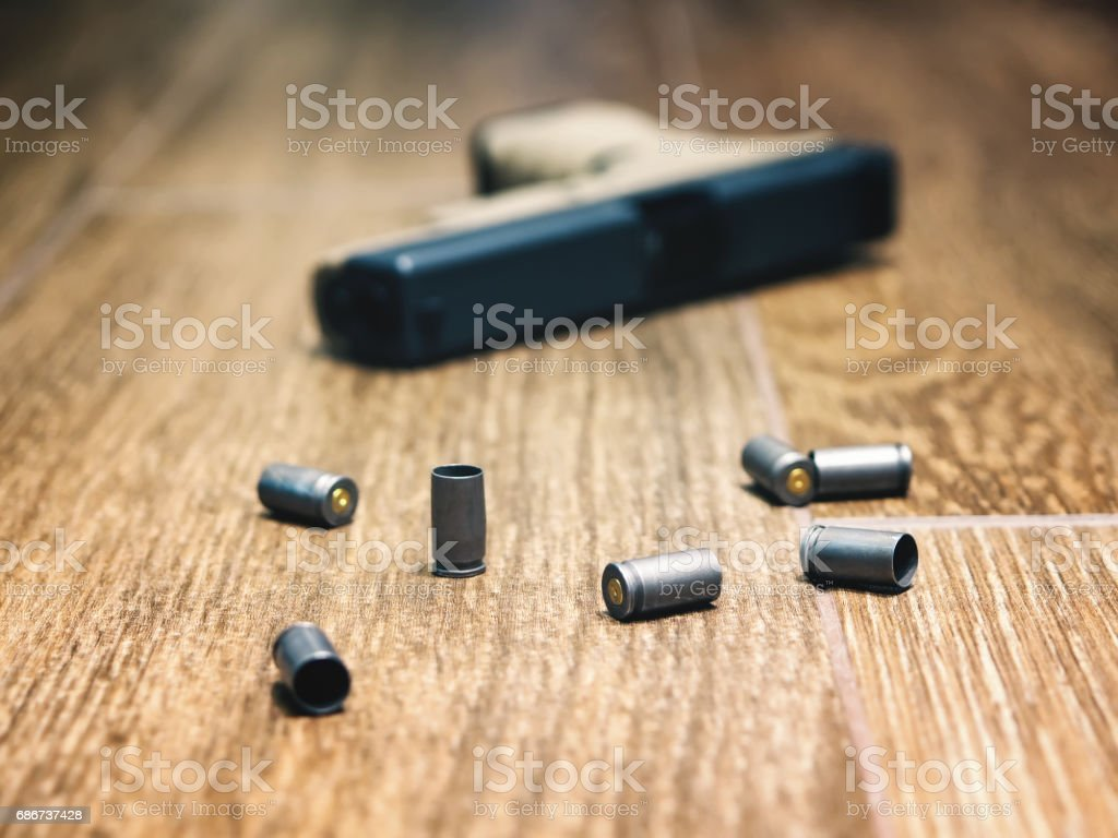 Defocused 9mm semi-auto pistol on the floor surrounded by spent shells.'nAttention: very shallow depth of field stock photo