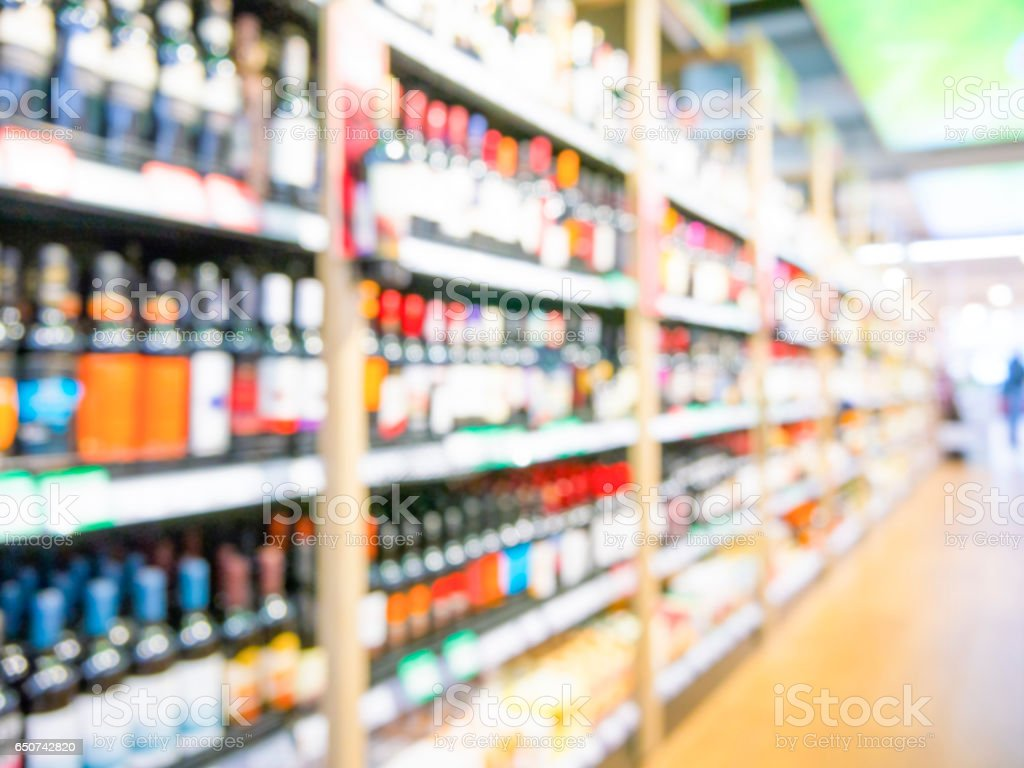 Defocused blur of supermarket shelves with bottles of alcohol. Blur...