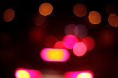 Defocused, blurry back lights of a car at night