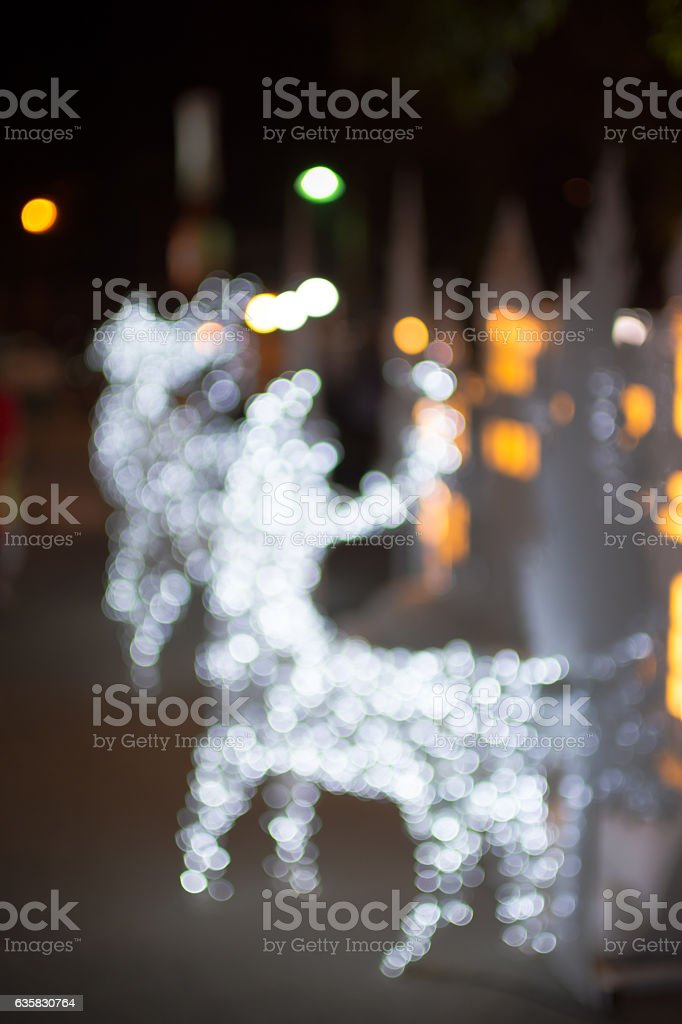 Defocused bokeh lights of christmas deer. Christmas day background. stock photo
