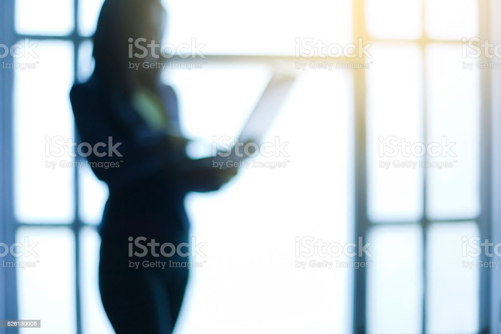 Defocused business woman standing near window and using laptop. stock photo