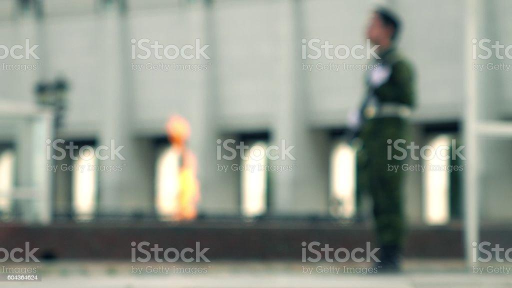 Defocused eternal flame memorial and armed guard. Bokeh background shot stock photo