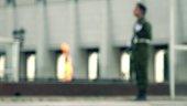 Defocused eternal flame memorial and armed guard. Bokeh background shot