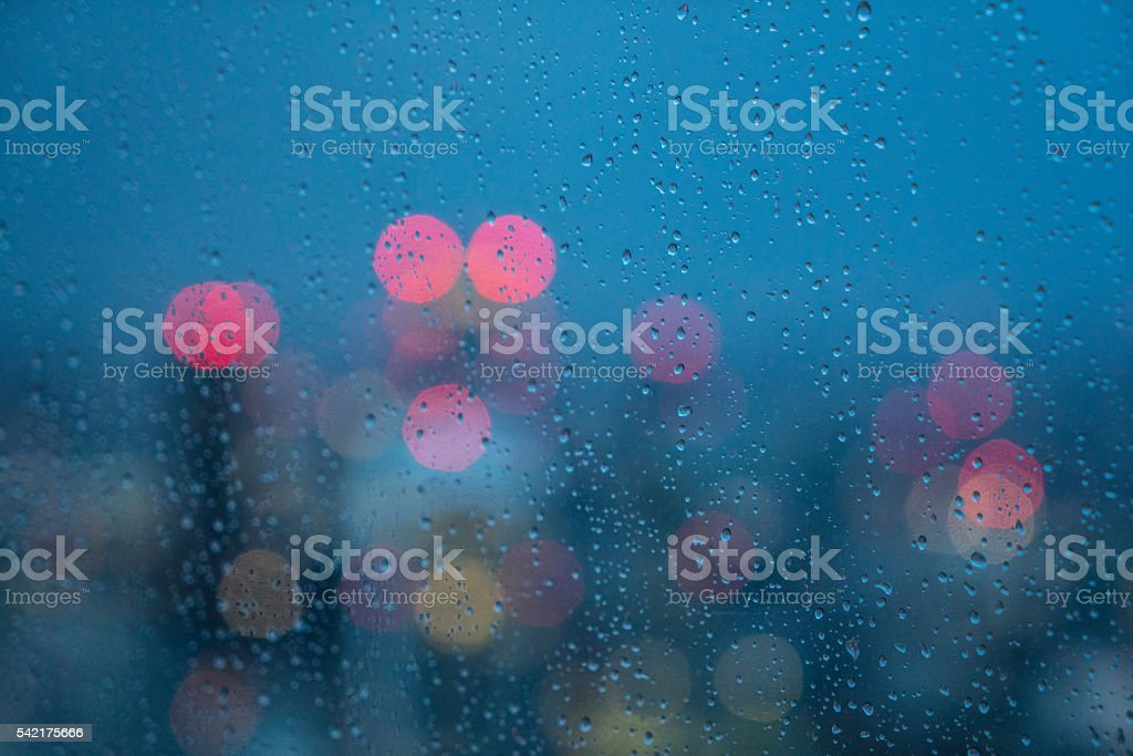 Defocused lights and water droplets on rainy wet window stock photo