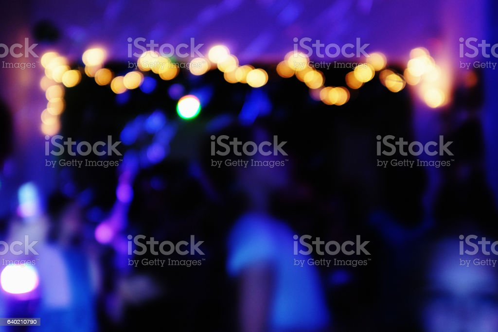 Defocused nighttime party scene in deep blue with bright lights stock photo