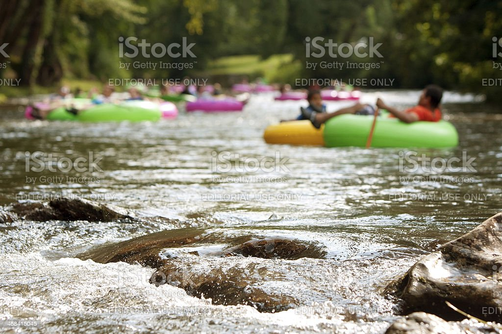 Defocused People Tubing Down RiverApproach Boulders In Focus stock photo