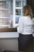 defocused photo of businesswoman standing by the window