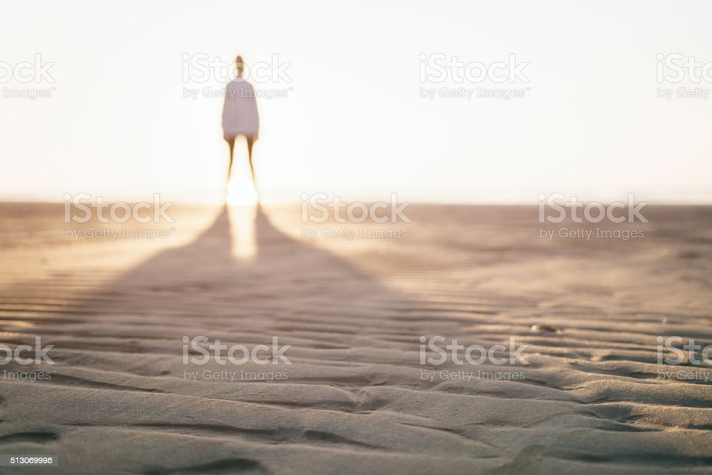 defocused photo of girl standing on beach stock photo
