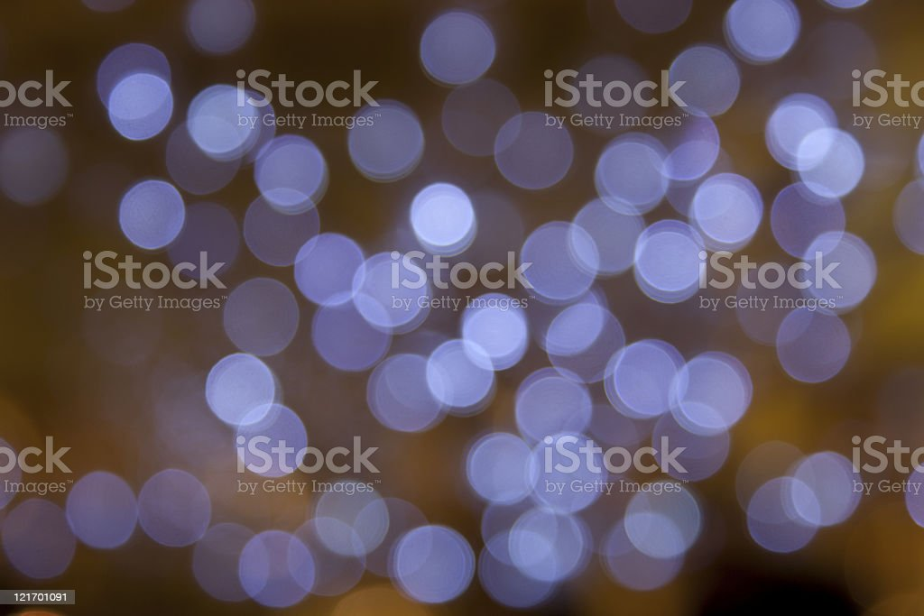 defocused purple light dots against dark/gold background royalty-free stock photo