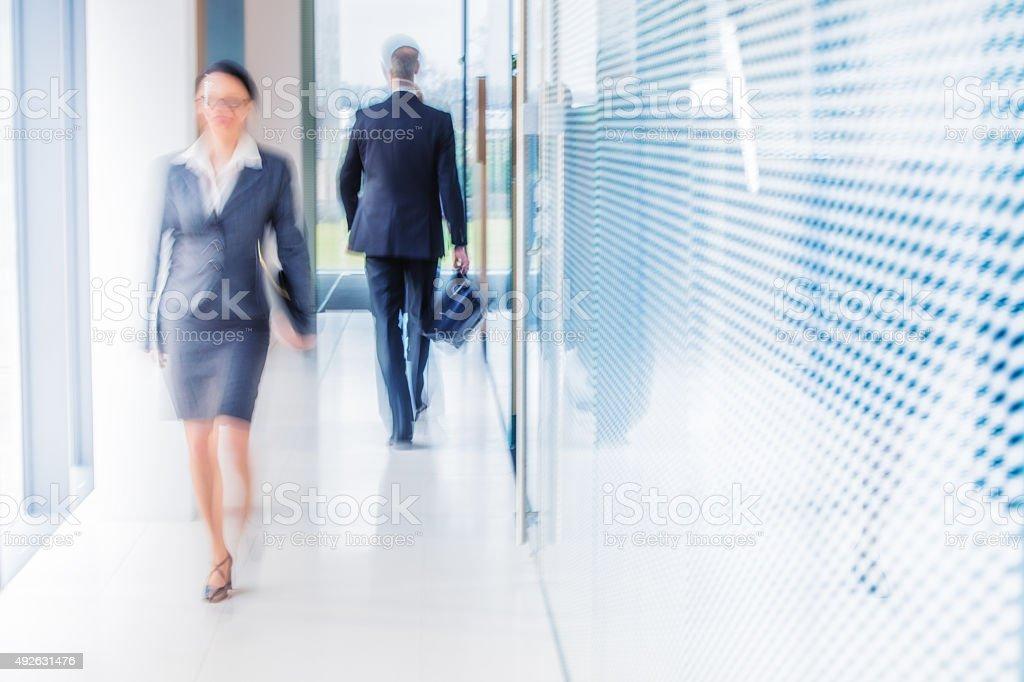 Defocused shot of business people walking in modern office corridor stock photo