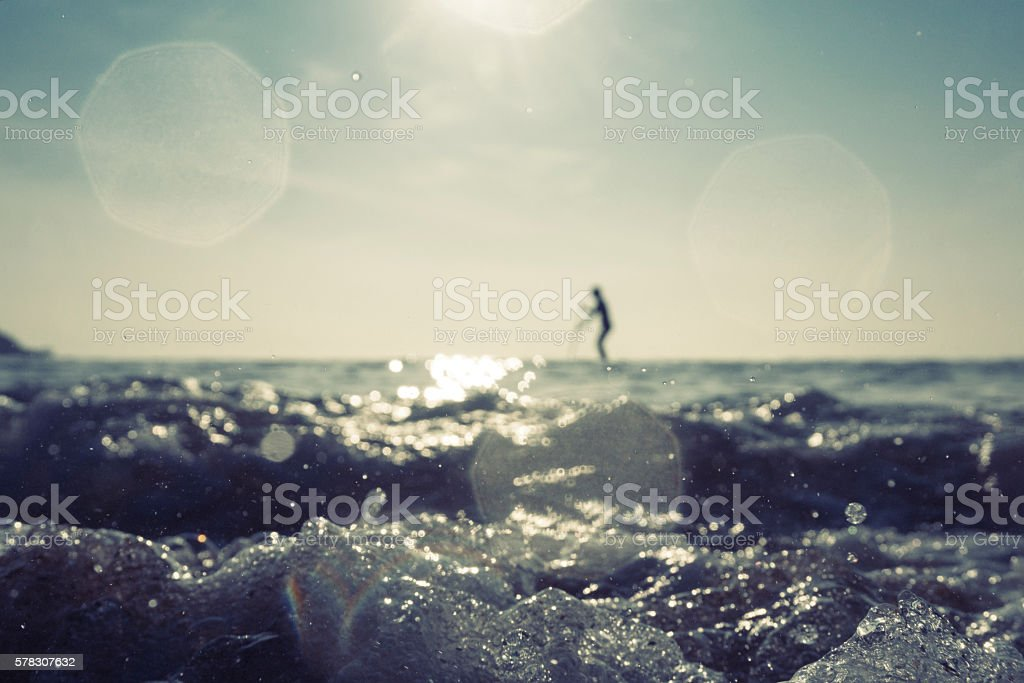 defocused SUP Boarder silhouette at Fistral Beach, Newquay June stock photo