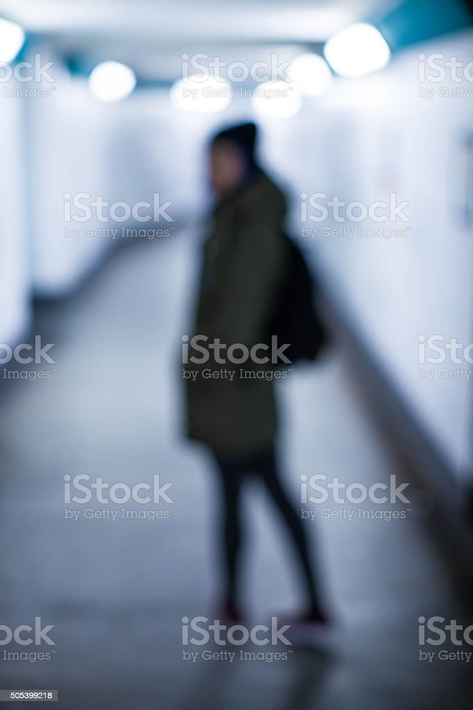 Defocused woman walks into the bright tunnel subway stock photo
