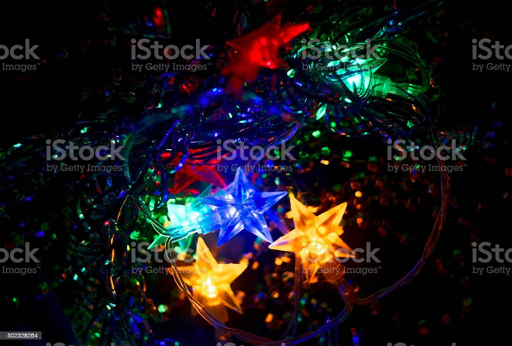 Defocused Xmass Garland with stars. Holiday Glowing Background. Shallow DOF stock photo