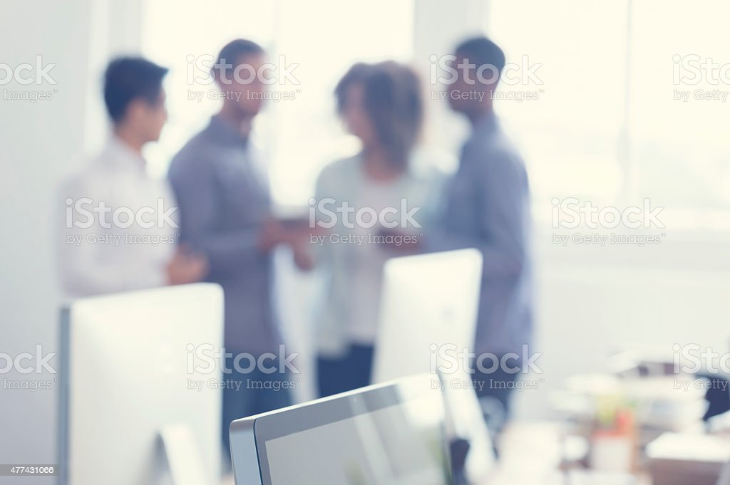 Defocussed image of 4 people working on a digital tablet. stock photo