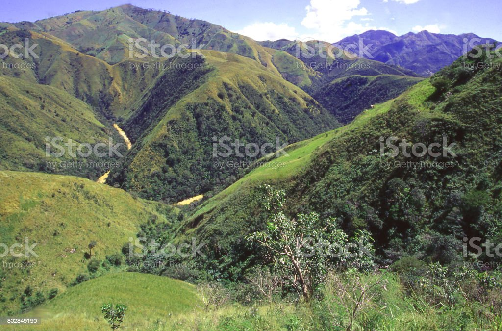 Degraded and eroded hills along the Haiti and Dominican Republic border with muddy Artibonite River in the Valley stock photo