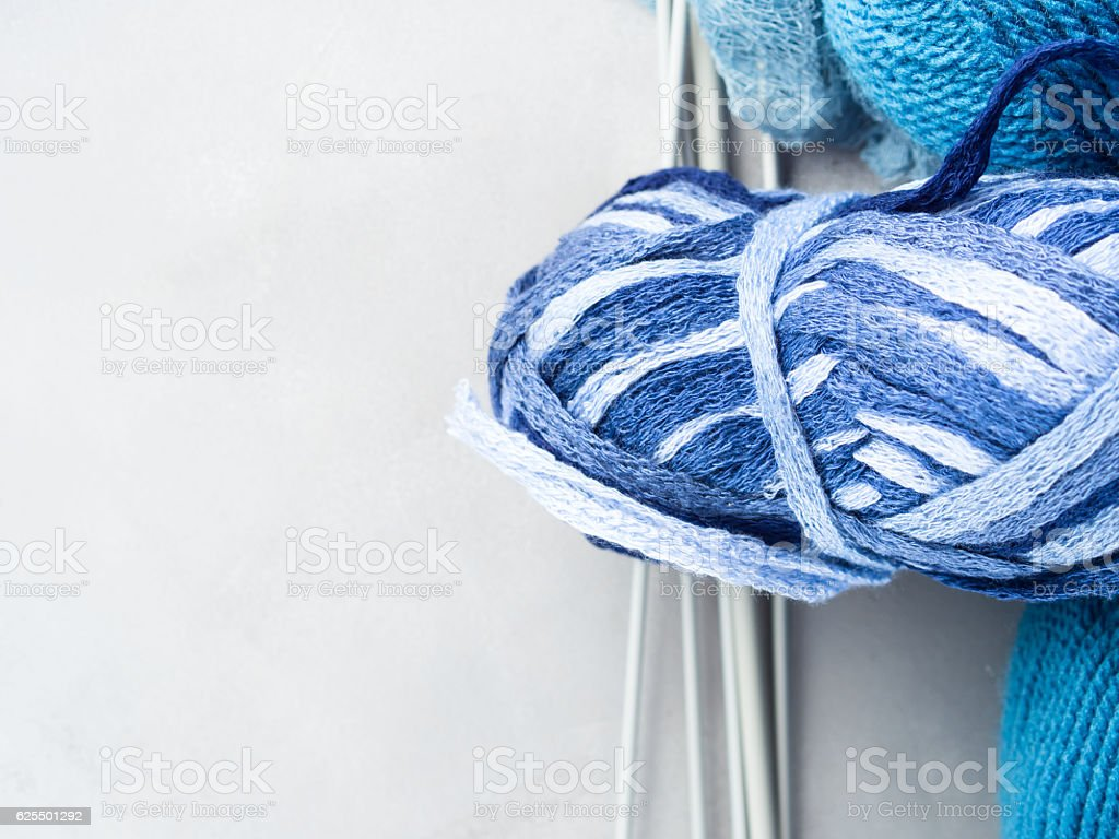 Degraded blue clew yarn with knitting needles. copy space stock photo