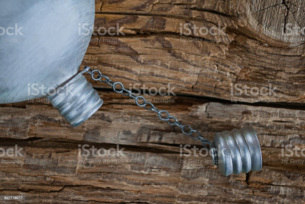 Dehydration concept. Empty vintage military aluminum canteen, water flask with cap unscrewed on coarse weathered wood background. stock photo