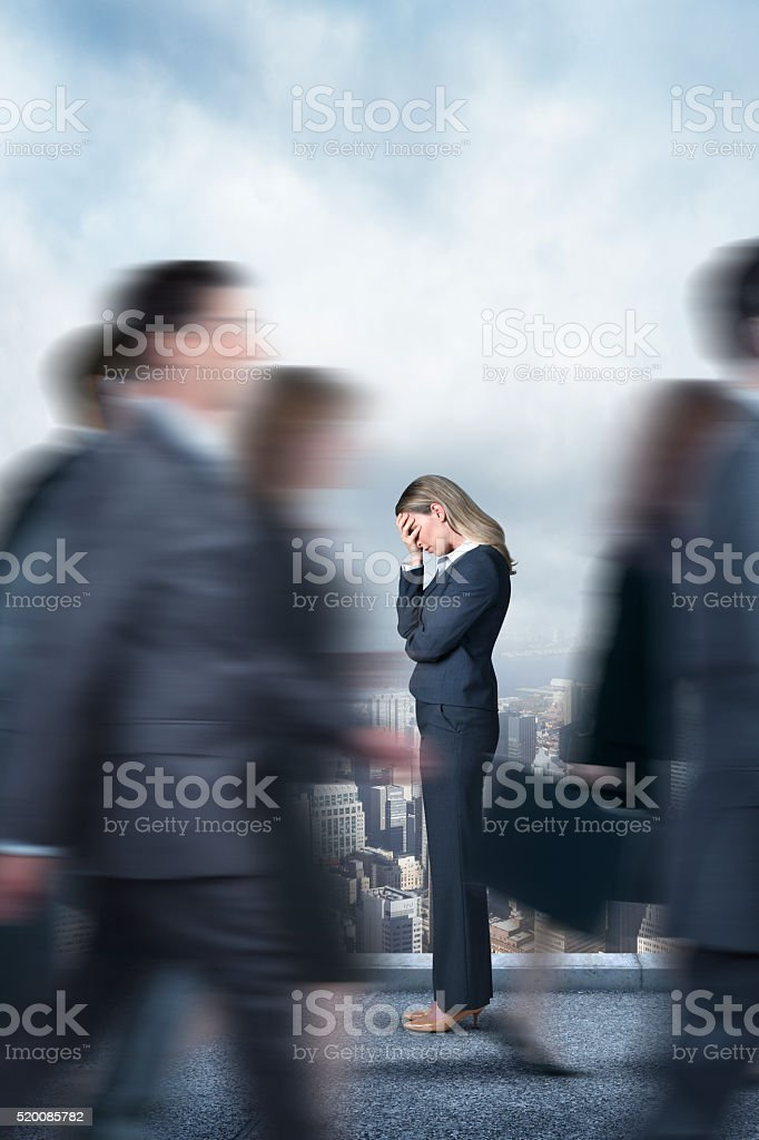 Dejected Businesswoman As Businesspeople Walk In Opposit Direction stock photo