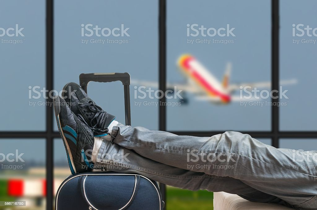 Delayed aeroplane concept. Tired passenger is awaiting airplane arrival. stock photo