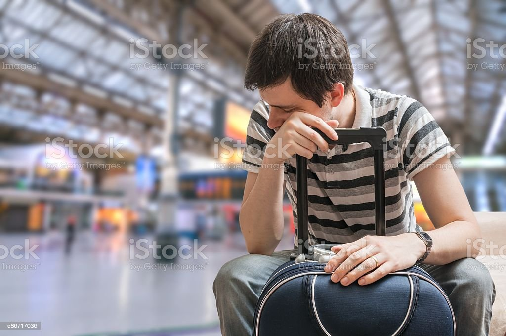 Delayed train concept. Tired passenger is sitting in train statition. stock photo