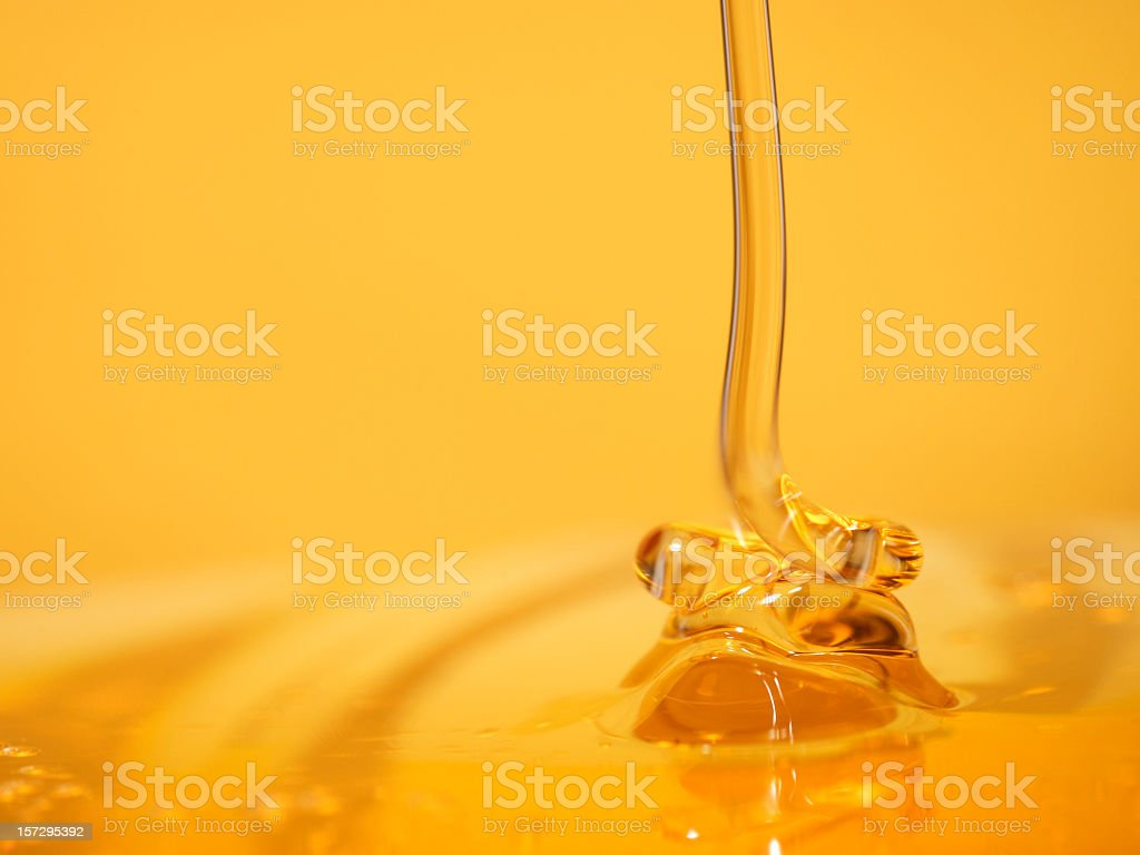 Delectable stream of honey flowing into a pool of honey stock photo