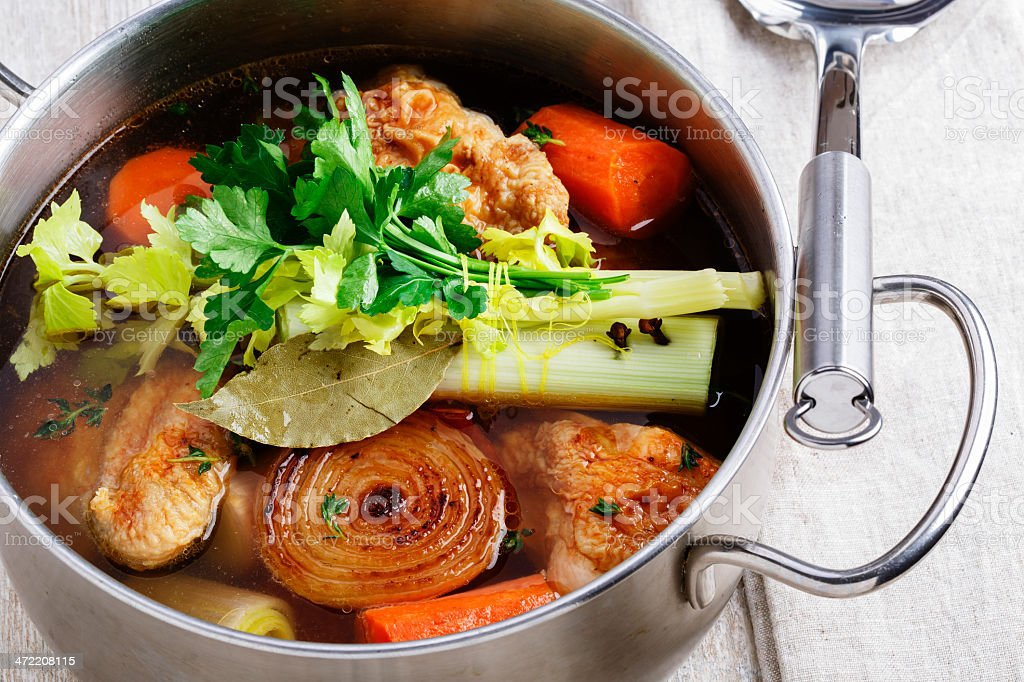 A delectable vegetable broth cooking in a silver pot stock photo