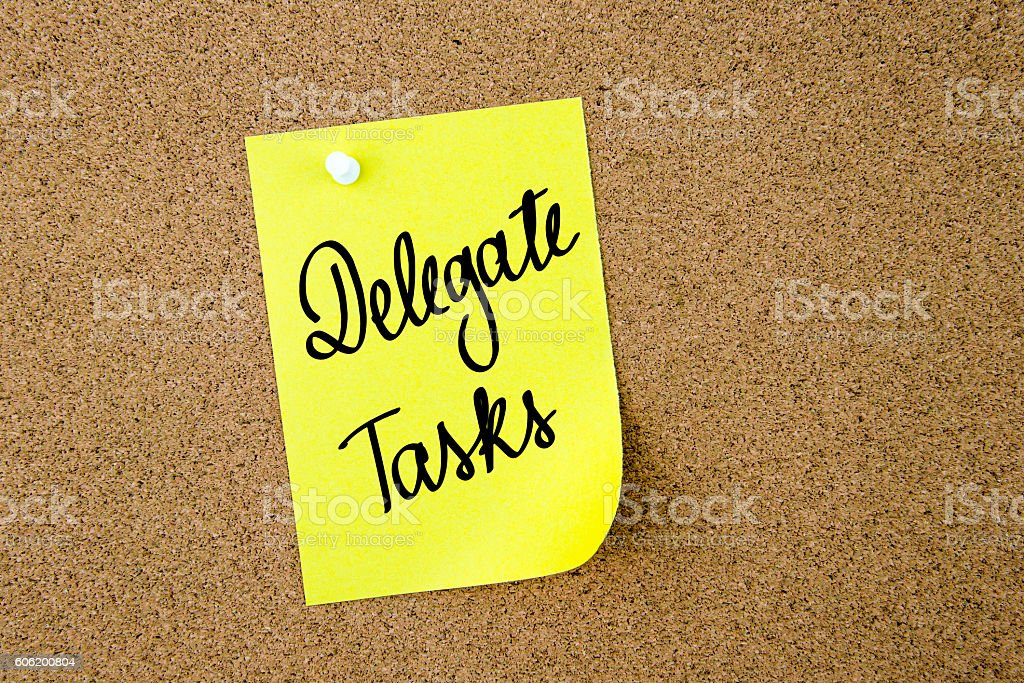 Delegate Tasks written on yellow paper note stock photo