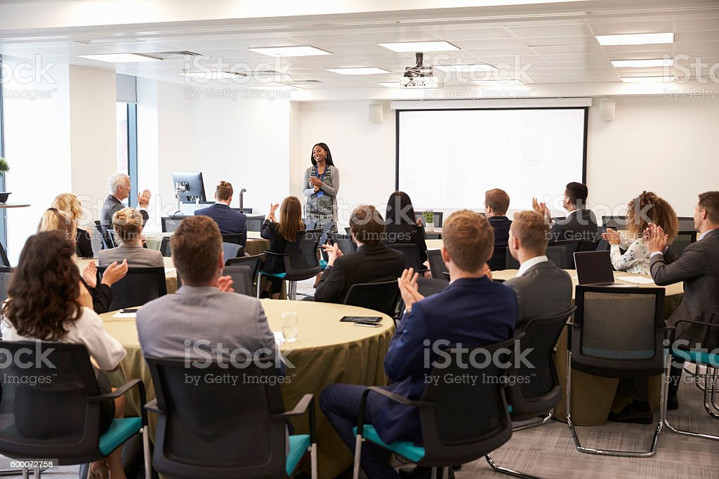 Delegates Applauding Businesswoman Making Presentation stock photo